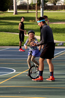 VonJon (right) helps a girl learning how to unicycle at Meadow Park.