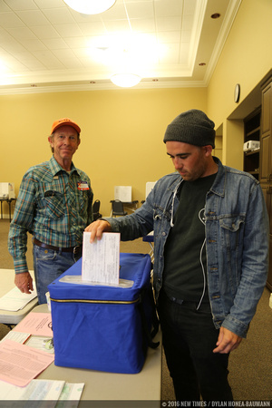 EMT Josh Cody drops his ballot while polling place Lead Inspector Bob Peak watches.