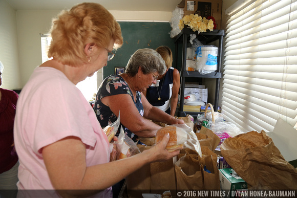 Debbie Madden (left), Kathy Turner (center) and Cherie Michaelson (right) put together paper bag dinners for the People's Kitchen.