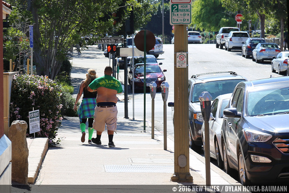 A reveler throws on a green shirt on his way to the bar.
